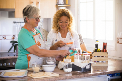 caregiver and senior woman cooking