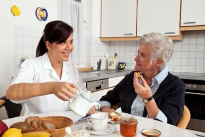 caregiver assisting senior woman in eating