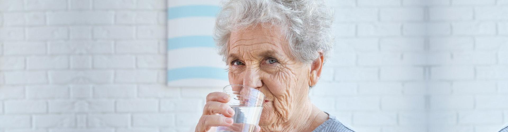an elderly woman drinking water